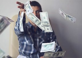 a young man throws money (dollars)
